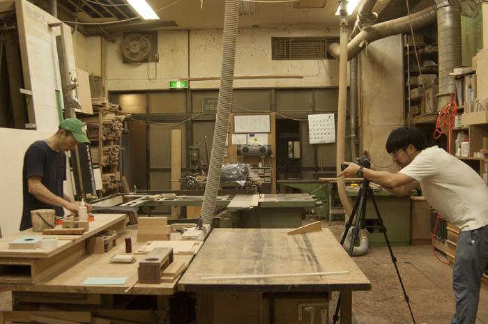 オリジナル楽器「か本」の製作シーン撮影を見守るメンバー