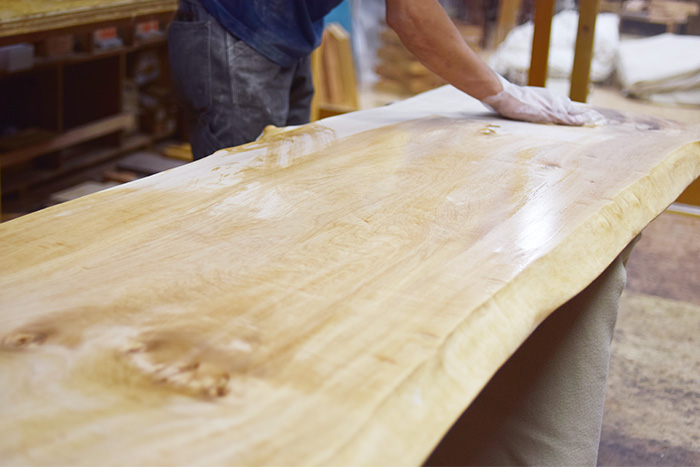 トチ一枚板天板をオイル塗装しているところ