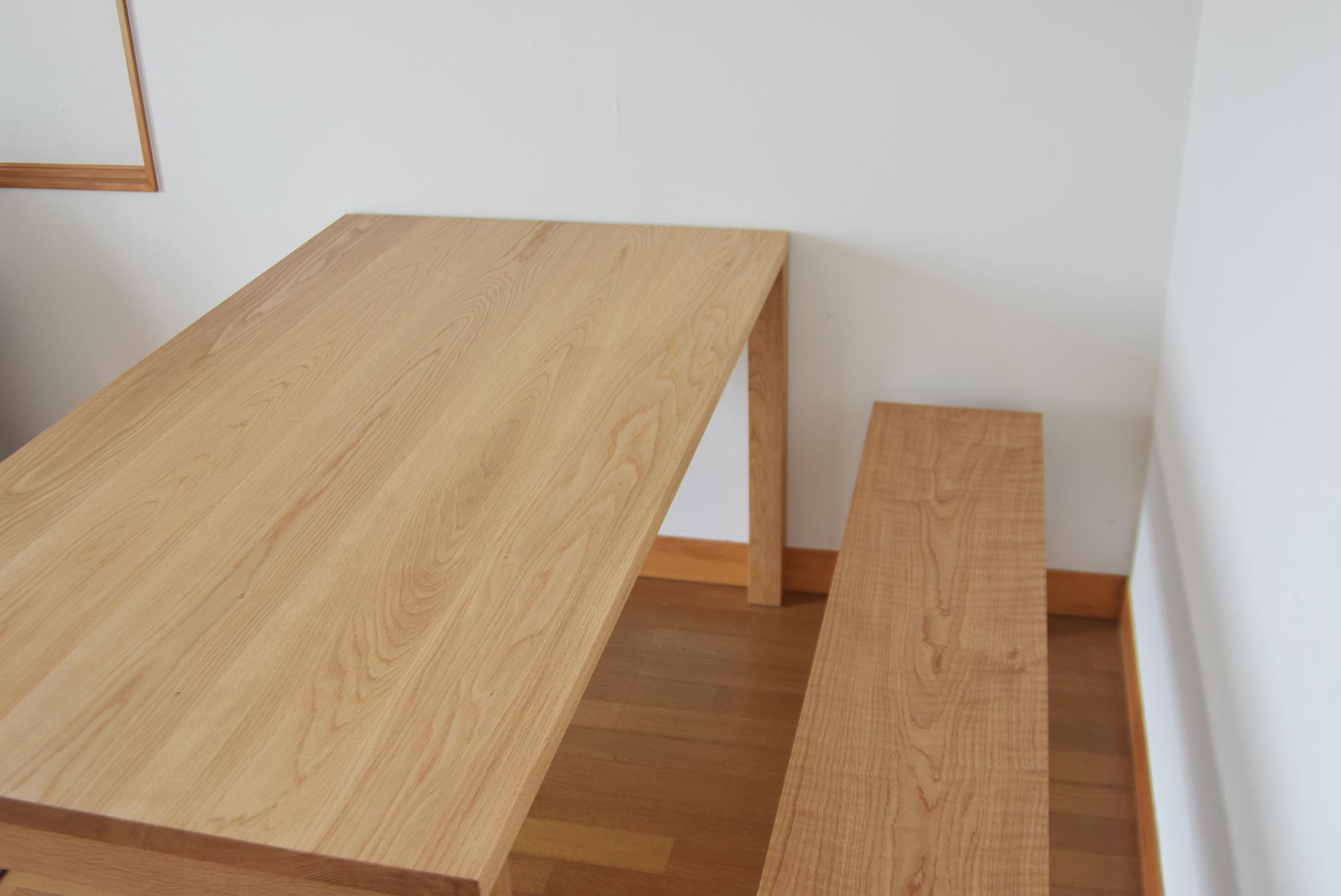 ナラ材の木目が穏やかな表情のテーブルとベンチ