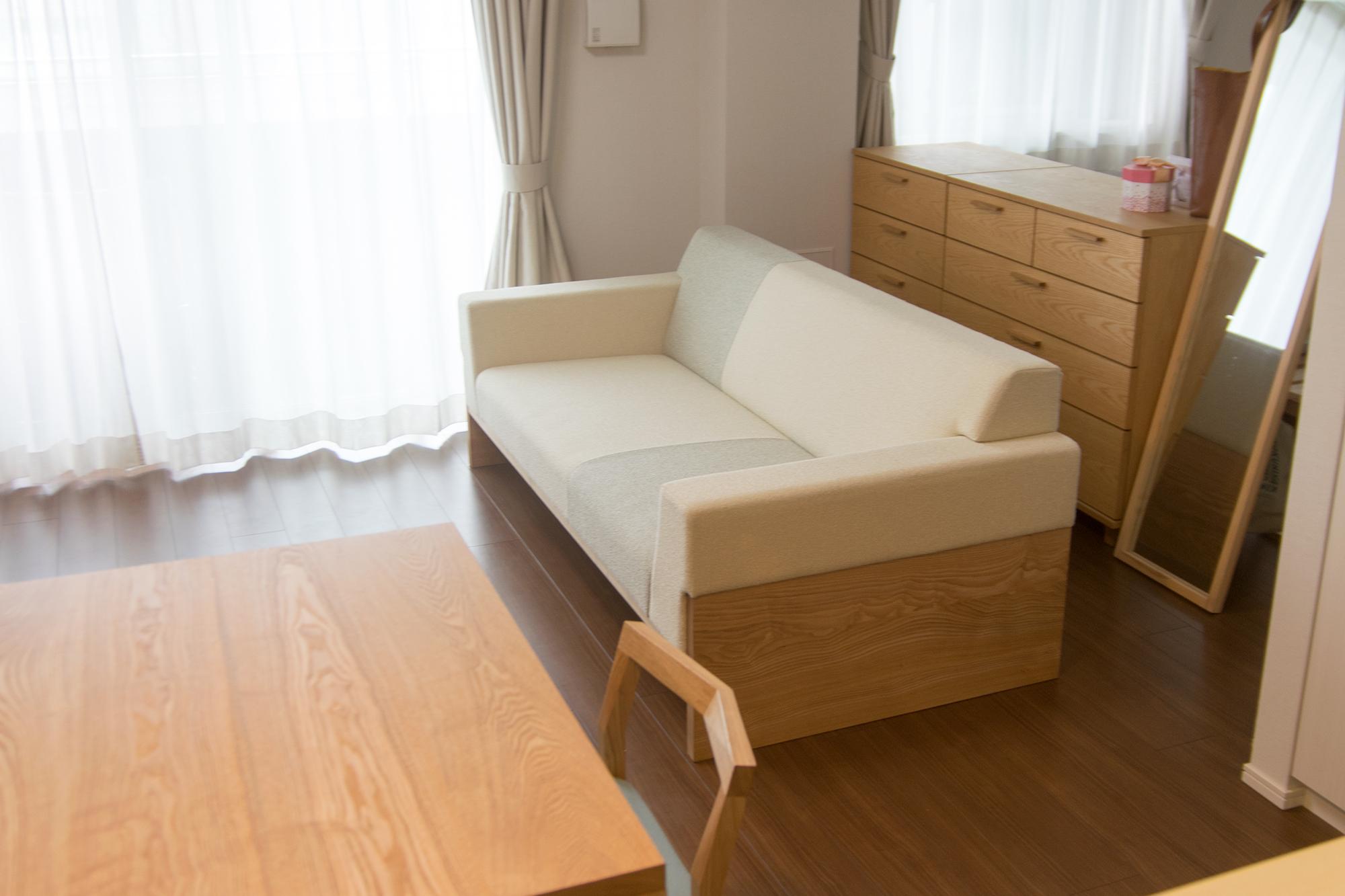タモ無垢材のベースにクッションを組み合わせた2人がけサイズのソファ