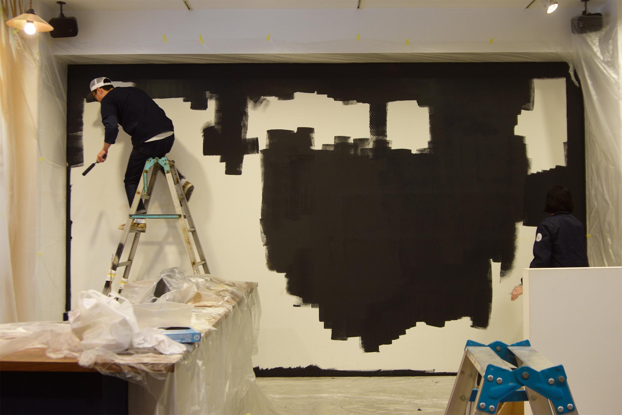 FACTORY RACLのために壁面を濃いグレーで塗装しているところ